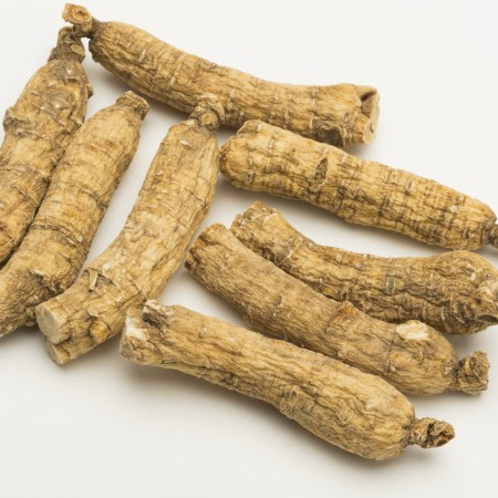 many dry ginseng roots on white background